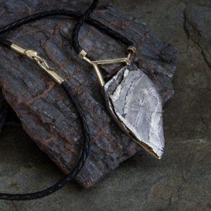 joya con un meteorito, oro y cuero